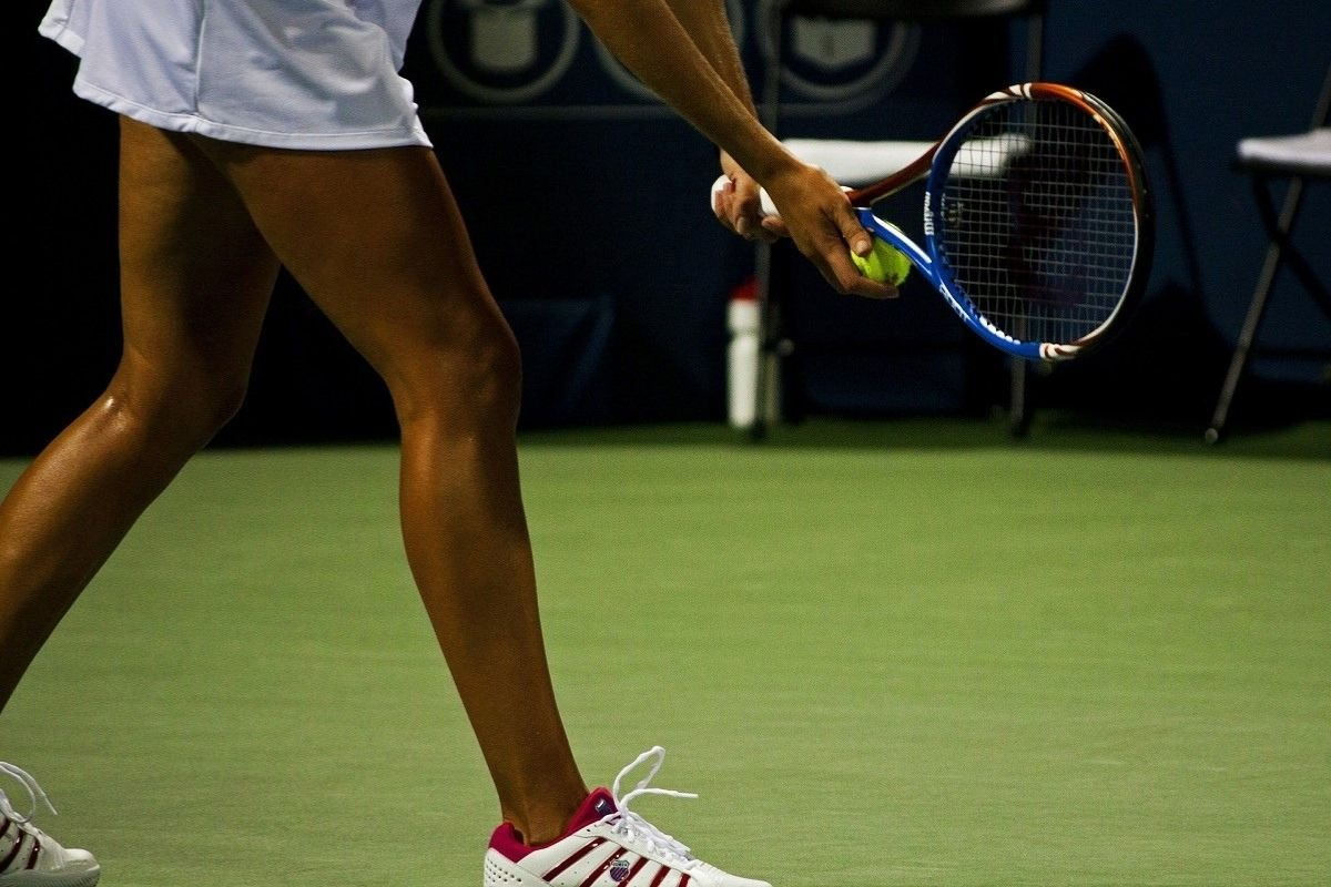 Photo of a female tennis player preparing to serve