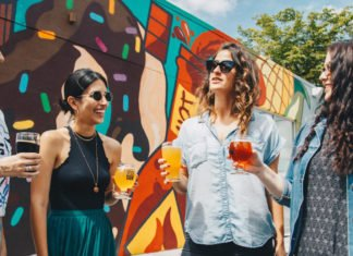 Image of people holding drinks and standing in the sun