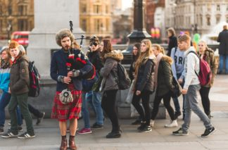Photo of a man playing bagpipes in a city near a monument