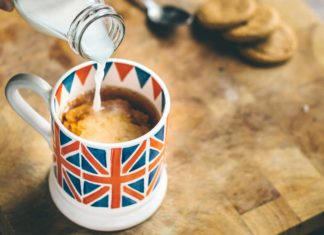 Photo of someone pouring milk into a mug of tea. The mug has a British flag on it. Tea is a great way to make British friends.