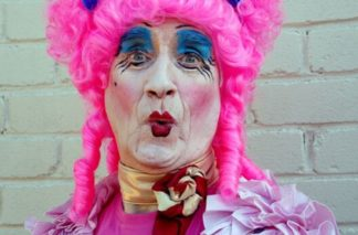 "Photograph of a man dressed up as a ""panto dame."" He is wearing heavy makeup and a bright pink wig."