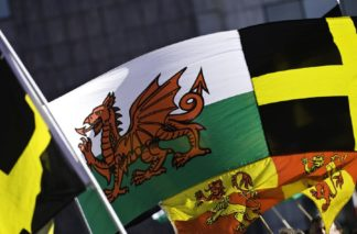 Picture of the Welsh flag and St David's flag being waved at St David's Day celebrations