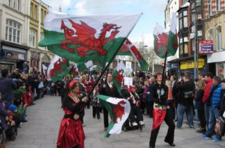 Photo of people waving Welsh flags at a St David's Day celebration