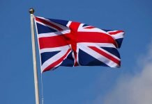 The UK flag, aka the Union Jack, flying in the air.