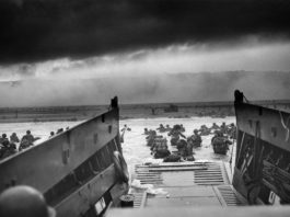 Black and white photograph of Allied soldiers landing in Normandy on D-Day