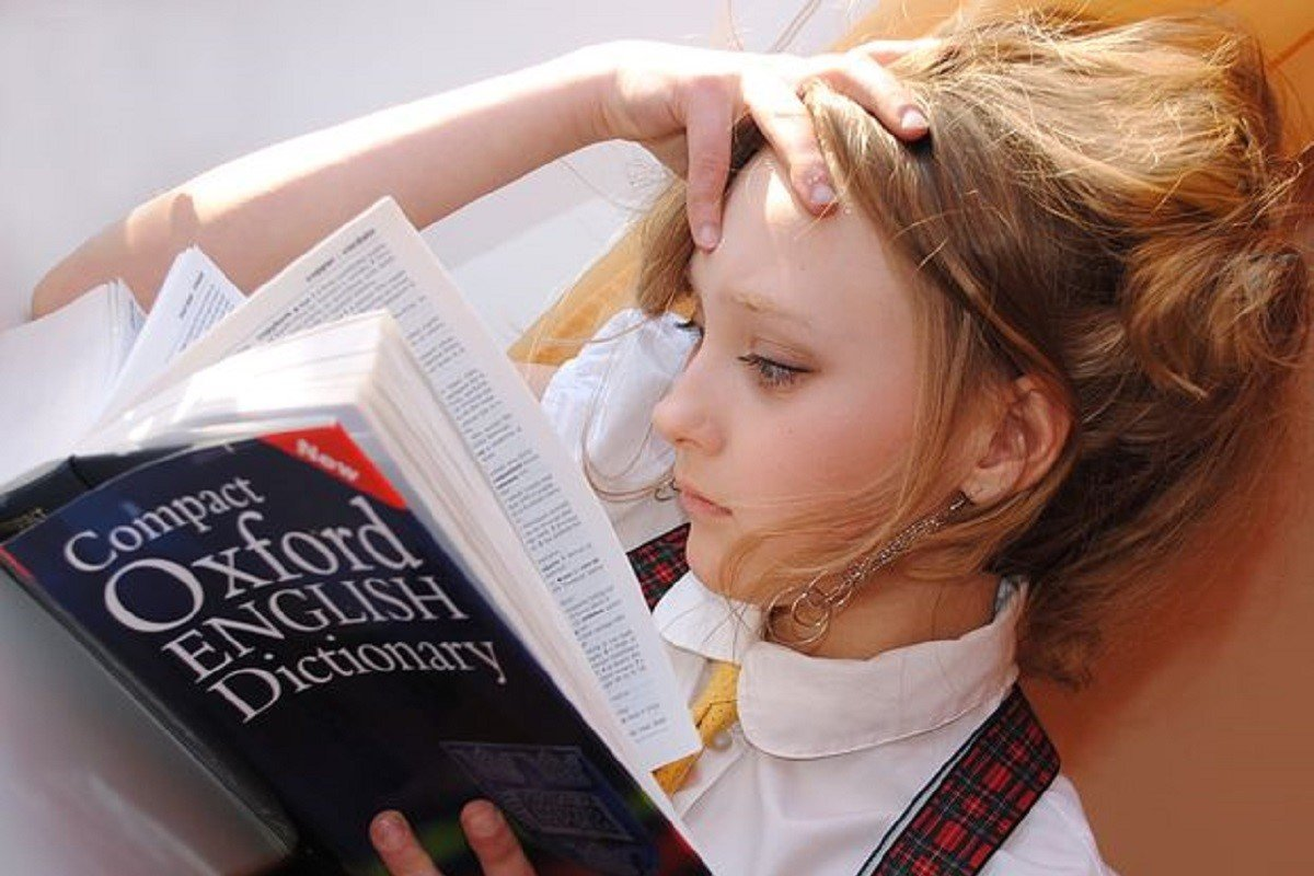 Girl rubbing her forehead whilst reading the Oxford English Dictionary