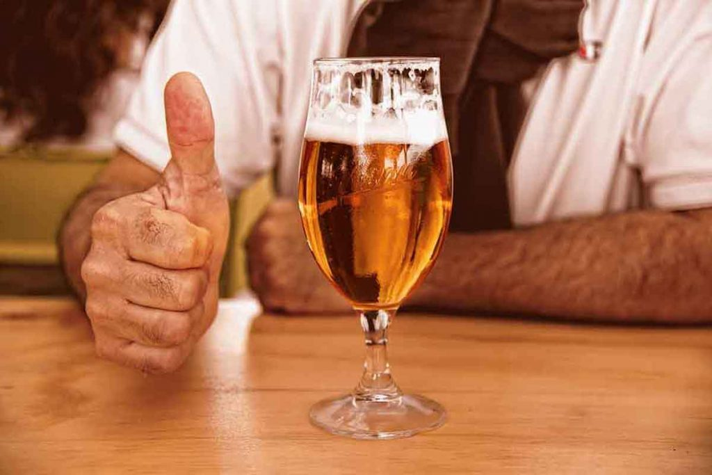Our guide on buying a round of drinks shows a man giving a thumbs-up to a glass of beer.