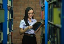 Photo of young woman reading in a library