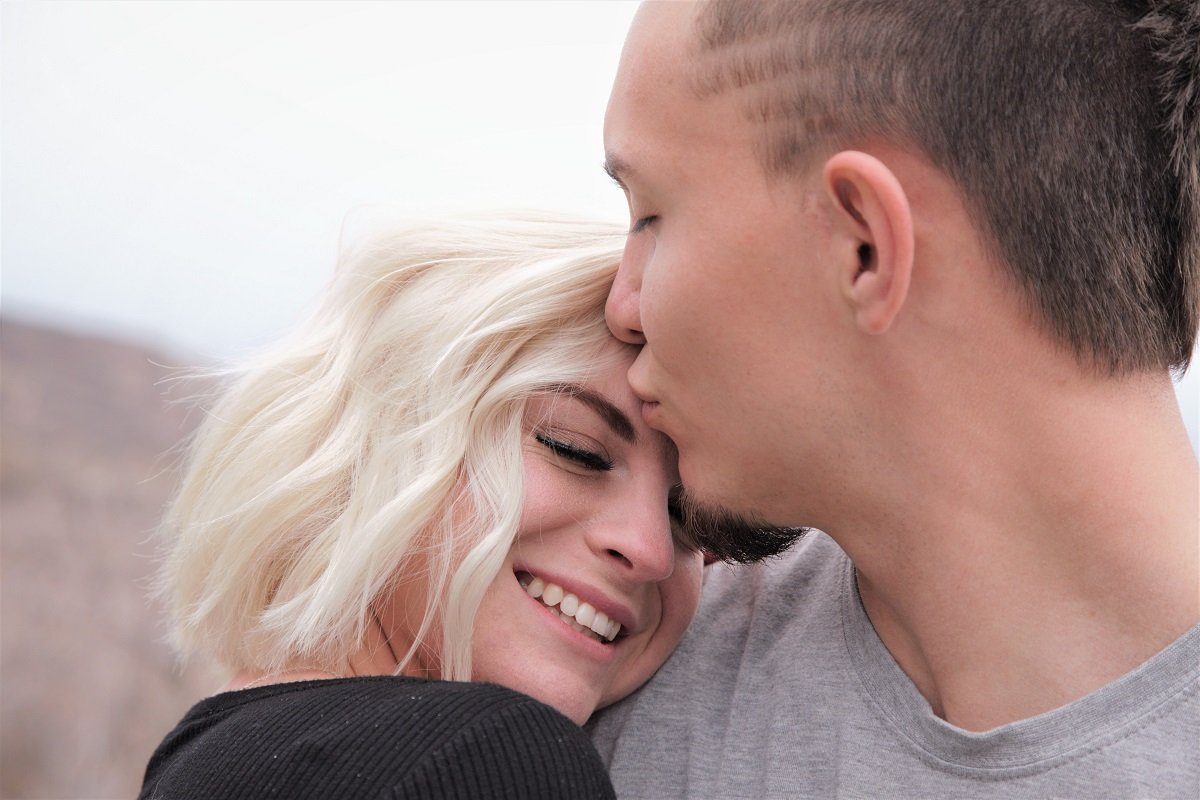 Image of man kissing woman's forehead