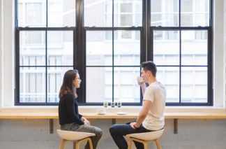 Photo of a woman and a man talking - conversation with a native speaker is a great way to improve your English