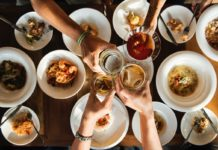 Photo of people clinking glasses over a table full of food