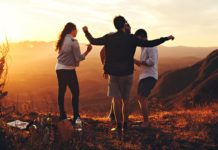 Photograph of friends standing on a hill