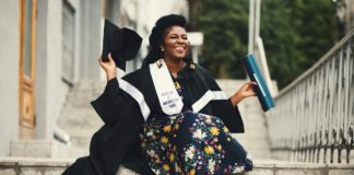 Photo of a woman wearing a cap and gown and holding a diploma