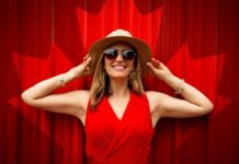 Photo of a woman wearing a red dress standing in front of a Canadian maple leaf