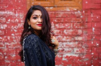 Photo of an Indian woman in front of a red brick wall