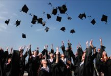 Photo of recent graduates throwing their caps into the air