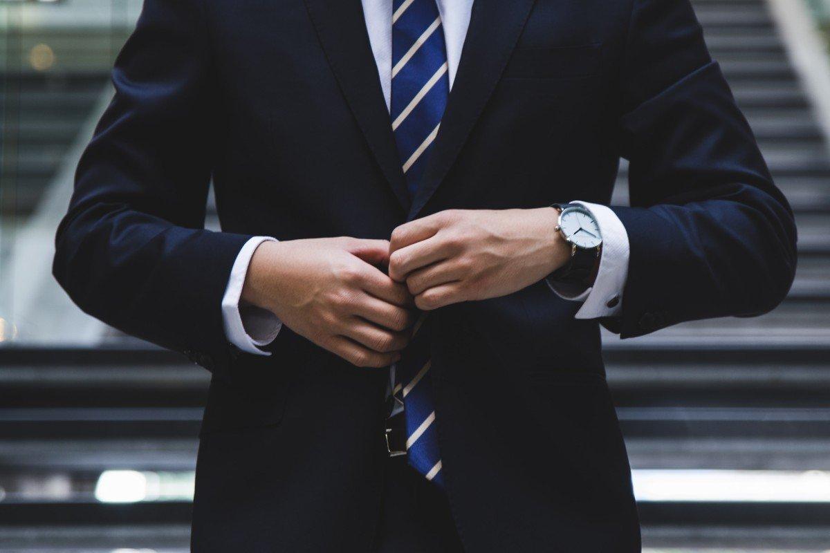 A businessman buttons up his jacket. after a job interview