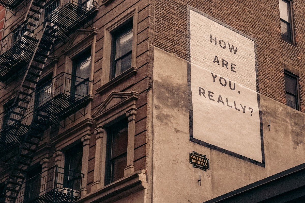 Billboard on the side of a building, saying how are you, really/