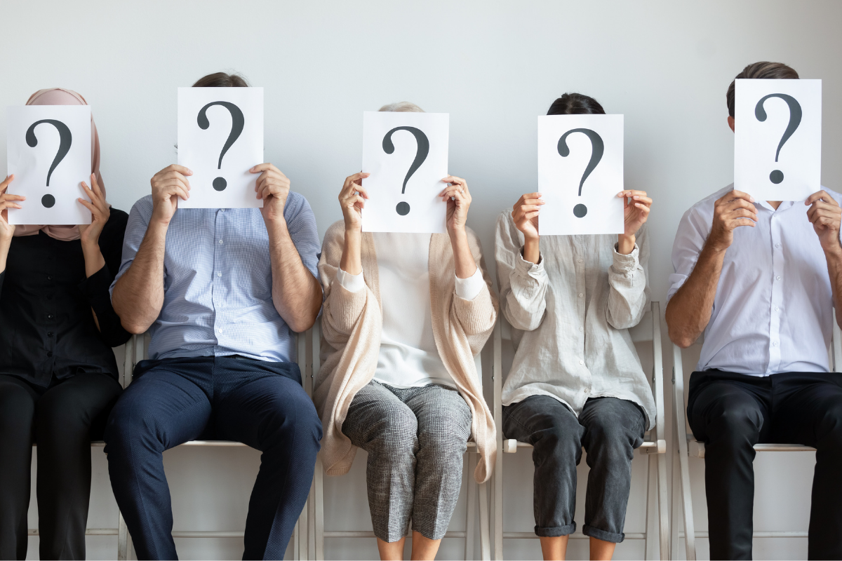 interviewees in a waiting room holding up question marks