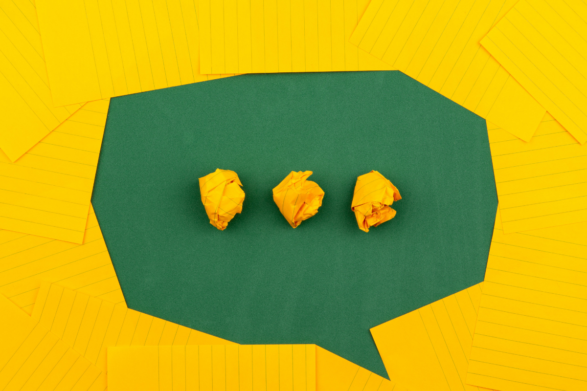 A speech bubble made out of green and yellow paper, with screwed up balls of paper making an ellipses