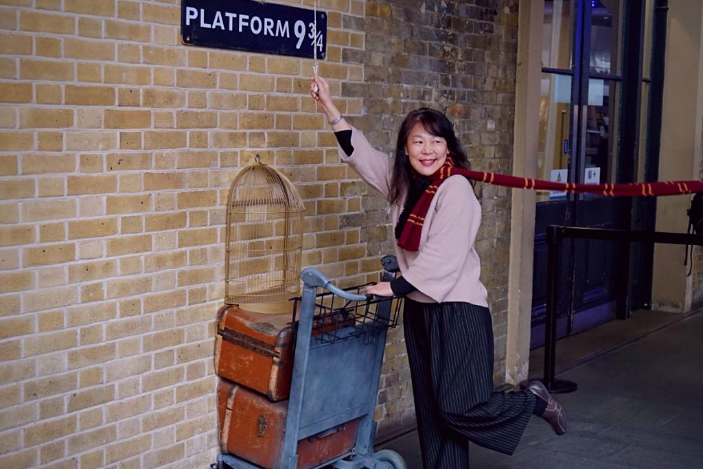 A Harry Potter fan poses at platform 9 3/4 at Kings cross station, London