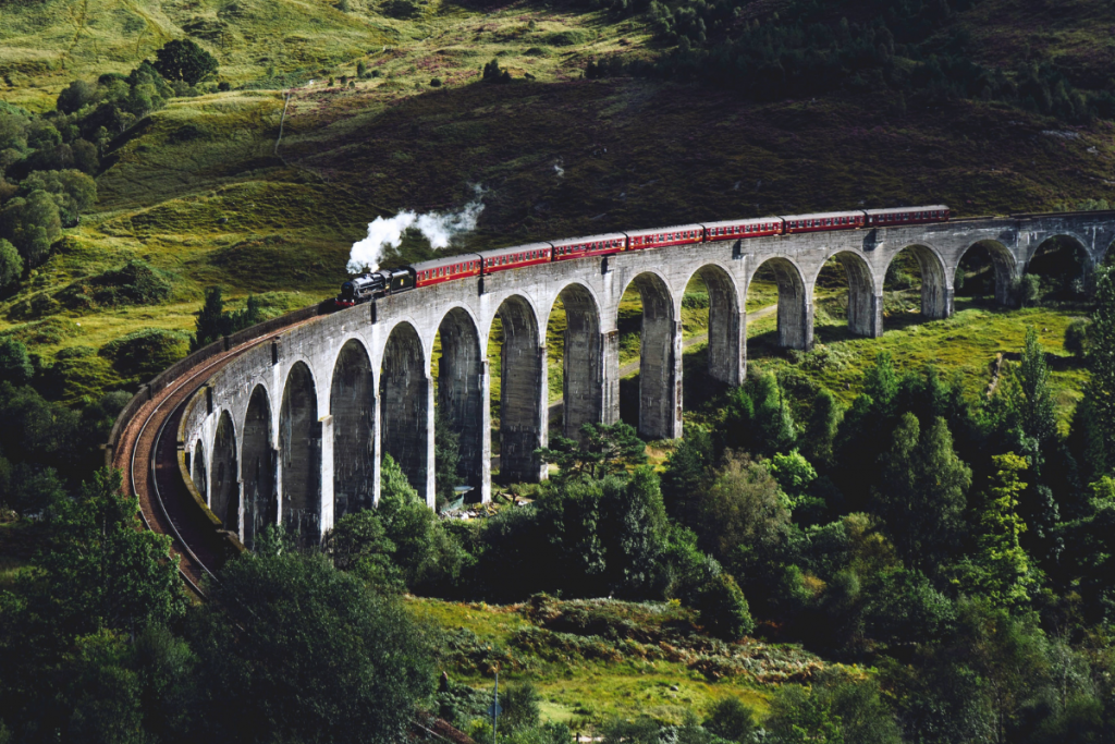 A steam train riding through countryside over a viaduct in Glenfinnan