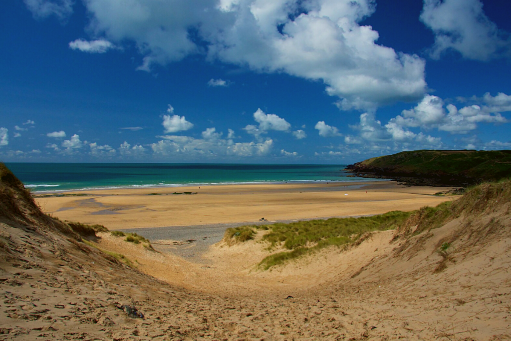 A sandy and deserted Freshwater West beach, with blue skies