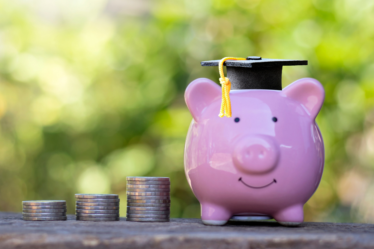 A piggy bank wearing a graduate hat next to a pile of coins