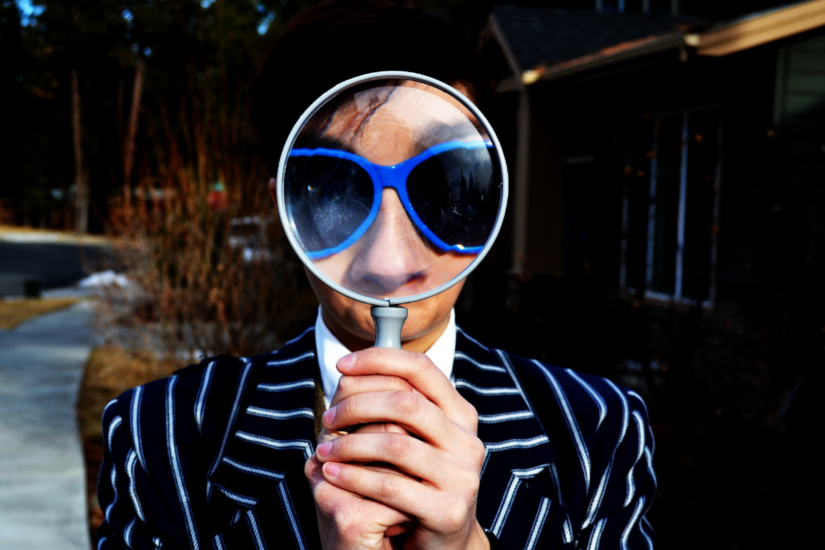 Person wearing a pinstripe suit holding a magnifying glass up to their eyes and looking into the camera